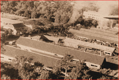 Los Banos internment camp from the air as liberation begins. Note smoke from markers for paratroopers.